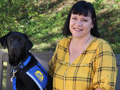 Woman named Cari with short brown hair and yellow plaid shirt sitting on a bench next to her black labrador dog named Rita with Canine Companions for Independence blue and yellow vest on.