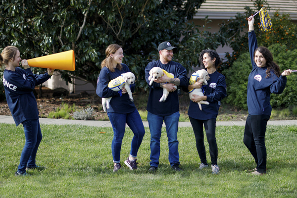 four adults wearing Canine Companions Jersey with puppies