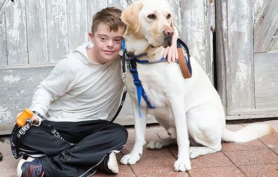 child sitting next to Canine Companions service dog