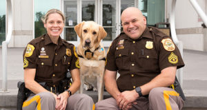 two police officers and a Canine Companions service dog