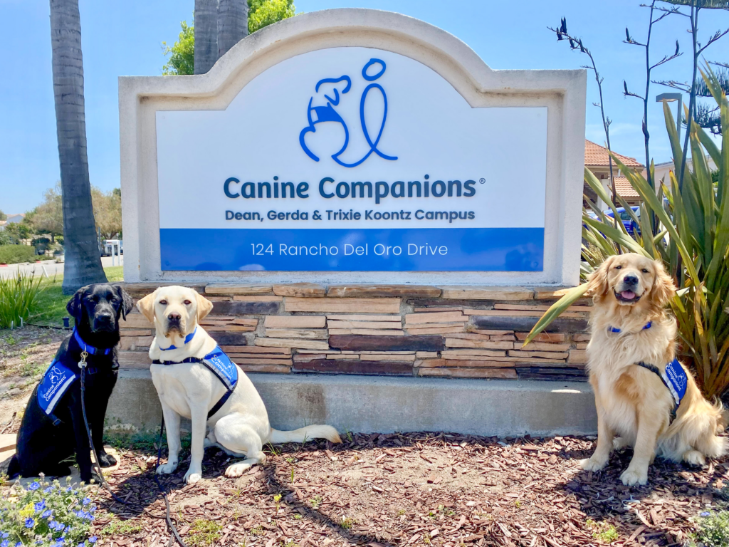 Three Canine Companions dogs sitting in front of the Southwest Region campus sign