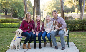 family with small dog and Canine Companions puppy