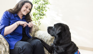 person doing sign language with a Canine Companions service dog
