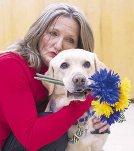 Person hugging Canine Companions service dog who is holding flowers in it's mouth