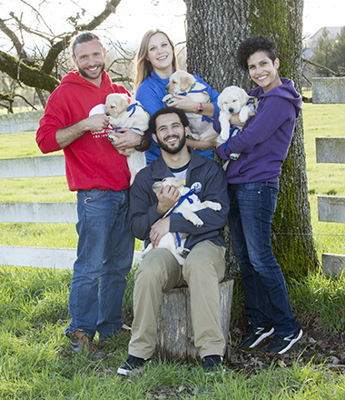 Group of 4 people in colored sweatshirts holding cream colored puppies