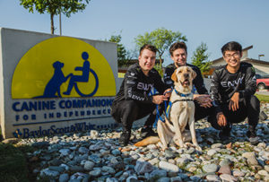 three people and a Canine Companions service dog
