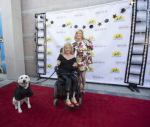 two people and a Canine Companions service dog on a red carpet