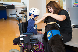 little boy in wheelchair next to a woman, petting a Canine Companions dog