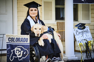 person wearing graduation gear with Canine Companions service dog over her lap