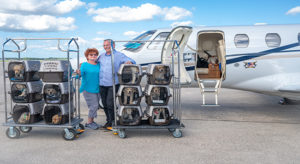 two people standing in front of plane with crates of puppies