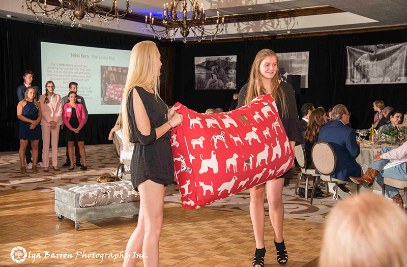 two people carrying a red dog bed