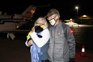 two people at airport holding Canine Companions puppy