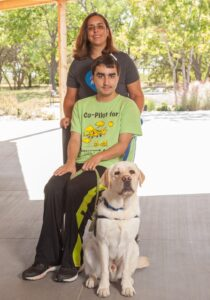 mother and son with yellow service dog