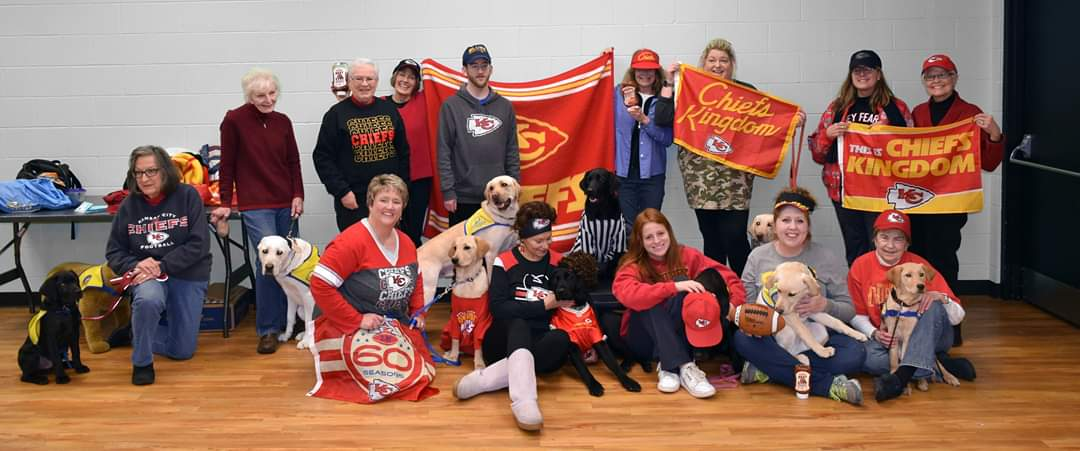 group of people with Chiefs merch and Canine Companions puppies