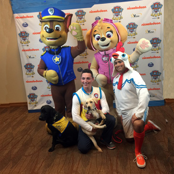 2 people and dogs stand with costumed Paw Patrol characters