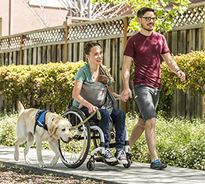 one person walking, one person sitting in wheelchair with a baby in a wrap and a Canine Companions service dog walking next to them