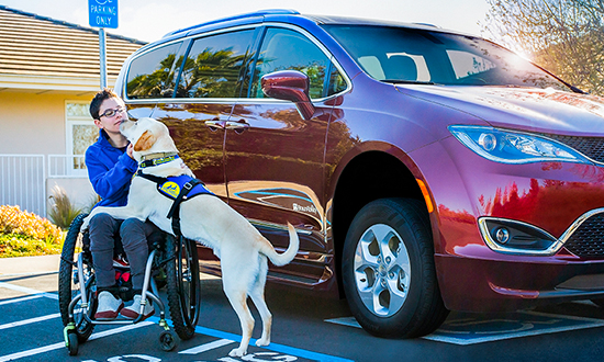 Woman in wheelchair next to her accessible mini van accompanied by her Canine Companions Service Dog