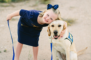 young girl next to assistance dog