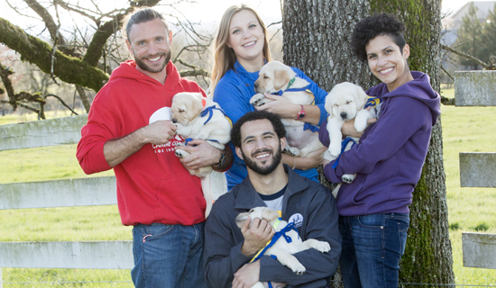 group of people holding Canine Companions puppies