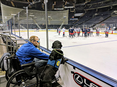 Canine Companions service dog next to a person sitting in a wheelchair at an ice rink