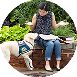 Woman with a book on her lap talking to dog