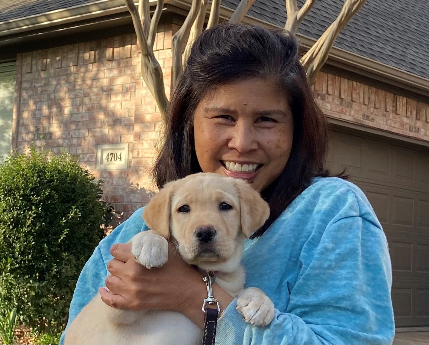 woman holding a yellow puppy