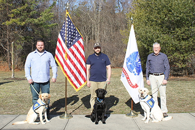 three people with Canine Companions service dogs