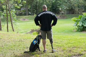 person wearing SpiritJersey standing next to Canine Companions service dog