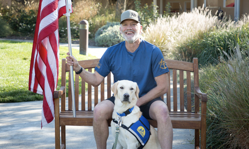 man sitting on a bench with a Canine Companions service dog