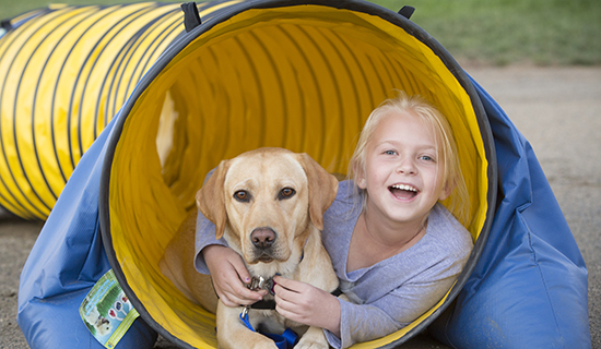 Girl with yellow dog in a tunnel