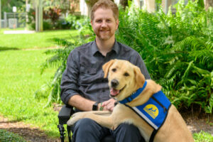 Joe seating in his wheelchair with service dog