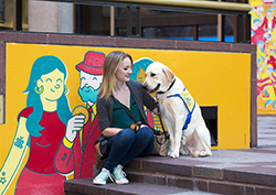 woman sitting in front of a mural with service dog