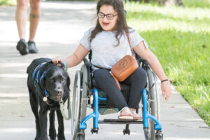 Leigh in a wheel chair walking her service dog on the sidewalk