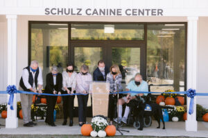 group of people cutting a ribbon at the Schulz Canine Center