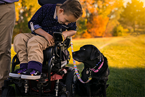 child sitting in wheelchair, leaning over towards Canine Companions service dog.