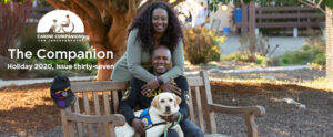 person sitting on a bench with a Canine Companions service dog across their lap and another person standing behind them.