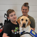 Young boy in wheel chair with his mom and service dog
