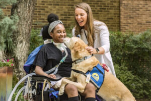 person standing next to person sitting in a wheelchair with a Canine Companions service dog next to them