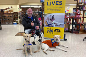 man sitting with two Canine Companions service dogs next to him