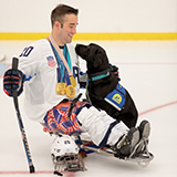 hockey player on ice with Canine Companions service dog