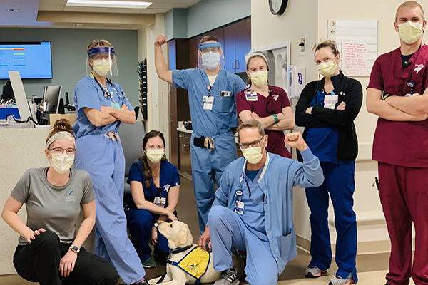 group of people in scrubs with Canine Companions puppy