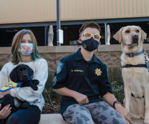 13 year old Miller and his yellow service dog, Bahama, sit with his younger sister Jac holding black Canine Companions puppy O'Sully