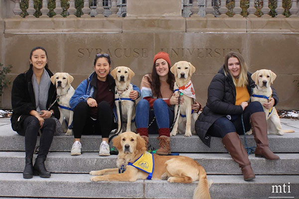 group of college age people with Canine Companions puppies