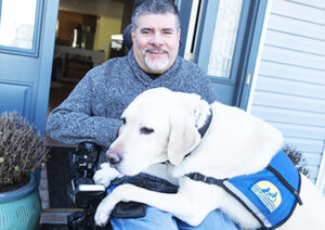 man sitting in chair with Canine Companions service dog