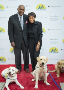 John and Joann Elliot posing on red carpet with three Canine Companions puppies