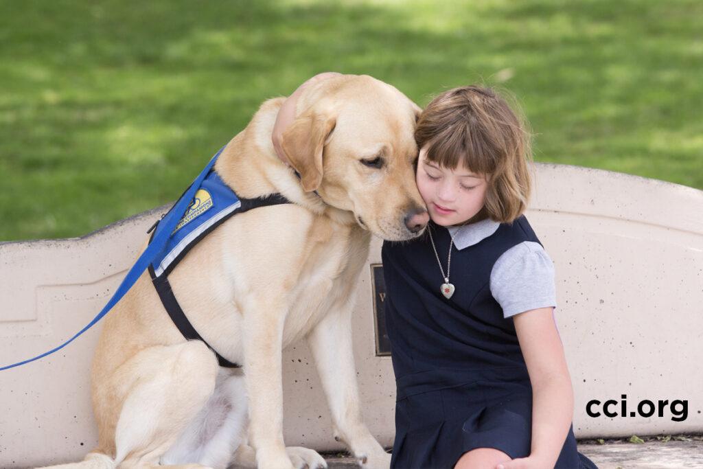 child hugging Canine Companions service dog