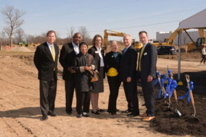 Board members standing in dirt field at ground breaking of the new North Central Campus