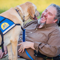 man with Canine Companions service dog face to face
