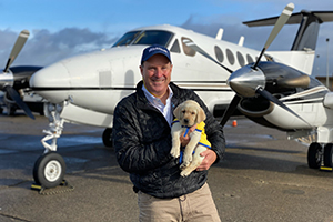 man holding a Canine Companions puppy in front of plane