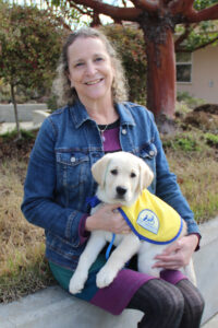 Rachel Meyer sits holding a yellow Canine Companions puppy on her lap